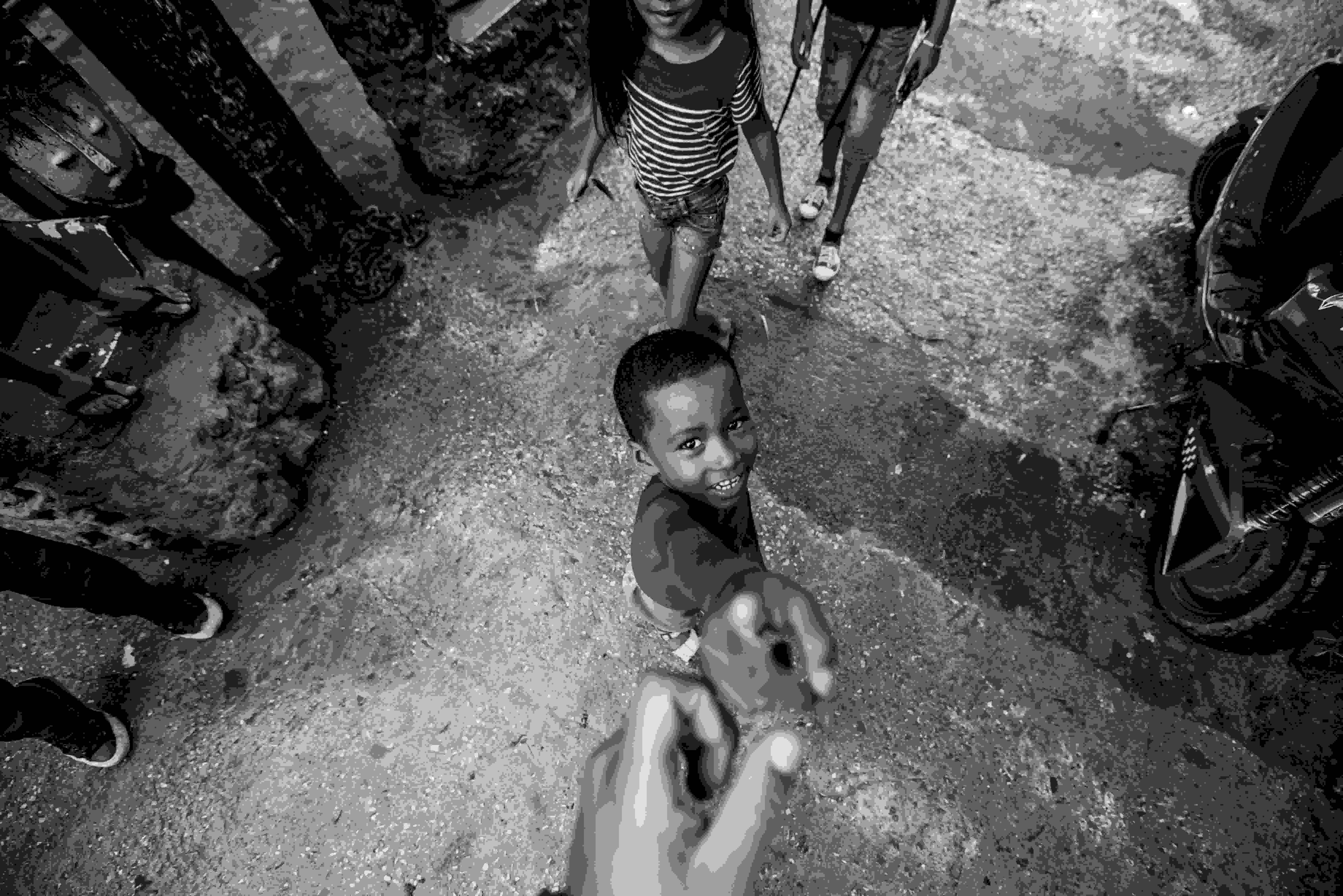 A picture of a young boy reaching up to hold someone's hand as an indication of impact created in someone's life